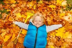 Glücklicher blonder Junge, der auf den Herbstlaub legt Lizenzfreies Stockfoto