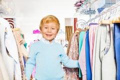 Glücklicher blonder Junge, der im Einkaufszentrum lacht Stockbilder