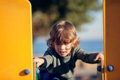 Glücklicher blonder Junge, der im Park auf gelbem Schieber spielt Stockbild