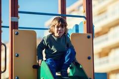 Glücklicher blonder Junge, der im Park auf gelbem und grünem Schieber spielt Stockfotos