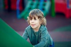 Glücklicher blonder Junge, der im Park auf grünem Schieber spielt Lizenzfreie Stockbilder