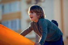 Glücklicher blonder Junge, der im Park auf orange Schieber spielt Stockbilder