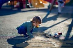 Glücklicher blonder Junge, der im Park mit Schmutz von einem Schlagloch spielt Lizenzfreies Stockfoto