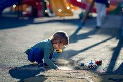 Glücklicher blonder Junge, der im Park mit Schmutz von einem Schlagloch spielt Lizenzfreie Stockfotografie