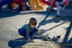 Glücklicher blonder Junge, der im Park mit Schmutz von einem Schlagloch spielt Stockfotografie