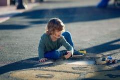 Glücklicher blonder Junge, der im Park mit Schmutz von einem Schlagloch spielt Stockbild