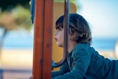 Glücklicher blonder Junge, der im Park stillsteht auf hölzernem Schieber spielt Lizenzfreies Stockfoto