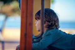 Glücklicher blonder Junge, der im Park stillsteht auf hölzernem Schieber spielt Stockfotos