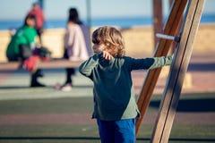 Glücklicher blonder Junge, der im Park stillsteht auf hölzernem Schwingen spielt Lizenzfreie Stockfotografie