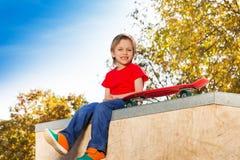 Glücklicher blonder Junge, der mit dem Skateboard allein sitzt Stockfotografie