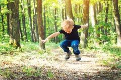 Glücklicher blonder Junge, der am sonnigen Tag auf Natur springt Stockfotografie