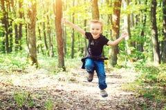 Glücklicher blonder Junge, der am sonnigen Tag auf Natur springt Stockfoto