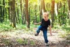 Glücklicher blonder Junge, der am sonnigen Tag auf Natur springt Lizenzfreies Stockbild