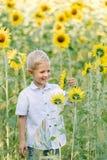 Glücklicher blonder Junge in einem Hemd auf Sonnenblumenfeld draußen Lebensstil, Sommerzeit, wirkliche Gefühle Stockbild