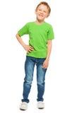 Glücklicher blonder Junge im grünen T-Shirt und im Denim Stockfotografie