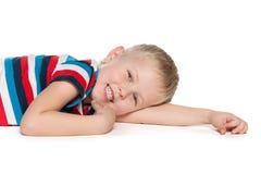 Glücklicher blonder Junge liegt auf dem Weiß Lizenzfreie Stockfotografie