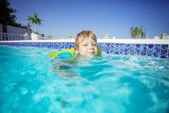 Glücklicher blonder Junge tragende floaties und draußen schwimmen Stockfoto