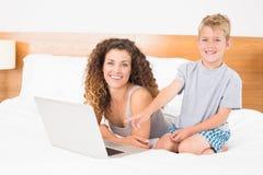Glücklicher blonder Junge und Mutter auf Bett unter Verwendung des Laptops Stockbilder