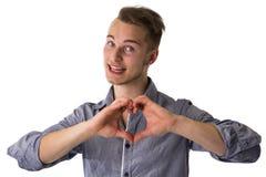 Glücklicher blonder junger Mann, der Herz- oder Liebeszeichenesprit tut Stockfotos