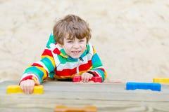 Glücklicher blonder Kinderjunge, der Spaß hat und auf Spielplatz im Freien klettert Lizenzfreie Stockfotografie