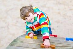 Glücklicher blonder Kinderjunge, der Spaß hat und auf Spielplatz im Freien klettert Stockbilder