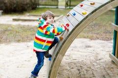 Glücklicher blonder Kinderjunge, der Spaß hat und auf Spielplatz im Freien klettert Stockbild