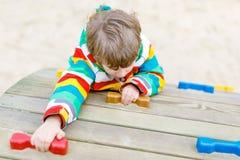 Glücklicher blonder Kinderjunge, der Spaß hat und auf Spielplatz im Freien klettert Lizenzfreie Stockbilder