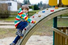 Glücklicher blonder Kinderjunge, der Spaß hat und auf Spielplatz im Freien klettert Lizenzfreie Stockfotos