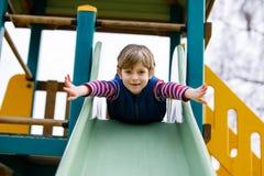 Glücklicher blonder Kinderjunge, der Spaß hat und auf Spielplatz im Freien schiebt Lizenzfreie Stockfotos