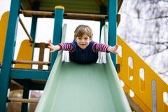 Glücklicher blonder Kinderjunge, der Spaß hat und auf Spielplatz im Freien schiebt Lizenzfreies Stockbild
