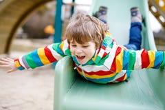 Glücklicher blonder Kinderjunge, der Spaß hat und auf Spielplatz im Freien schiebt Lizenzfreie Stockfotografie