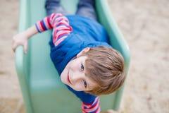 Glücklicher blonder Kinderjunge, der Spaß hat und auf Spielplatz im Freien schiebt Stockbilder