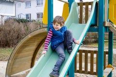 Glücklicher blonder Kinderjunge, der Spaß hat und auf Spielplatz im Freien schiebt Stockfotos