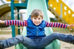 Glücklicher blonder Kinderjunge, der Spaß hat und auf Spielplatz im Freien schiebt Lizenzfreies Stockfoto