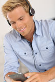 Glücklicher blonder Mann, der Musik mit Kopfhörer hört Stockfoto