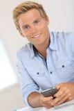 Glücklicher blonder Mann mit dem blauen Hemd, das einen Mitteilungstext sendet Stockbilder