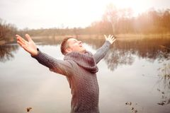 Glücklicher blonder Mann vor dem See, der seine Arme verbreitet Stockbild