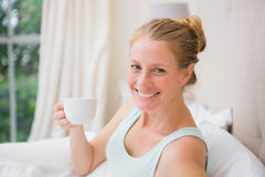 Glücklicher blonder trinkender Kaffee im Bett Stockfoto