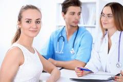 Glücklicher blonder weiblicher Patient nahe bei einigen Doktoren im Krankenhaus, das am Tisch sitzt Stockbild