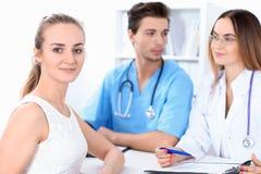 Glücklicher blonder weiblicher Patient nahe bei einigen Doktoren im Krankenhaus, das am Tisch sitzt Lizenzfreie Stockfotografie