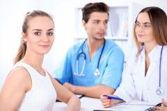 Glücklicher blonder weiblicher Patient nahe bei einigen Doktoren im Krankenhaus, das am Tisch sitzt Lizenzfreies Stockfoto