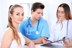 Glücklicher blonder weiblicher Patient nahe bei einigen Doktoren im Krankenhaus, das am Tisch sitzt Stockfotos