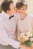 Glücklicher Bräutigam, der lächelnde blonde Braut mit Blumenstrauß auf der Backe küsst Frühlingsweg Lizenzfreies Stockbild