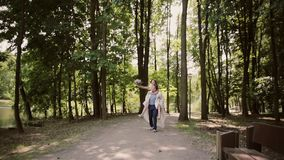Glücklicher Bräutigam läuft mit seiner lachenden Braut auf seinem zurück Glückliches Paar, das Spaß an ihrem Hochzeitstag hat ste stock video footage