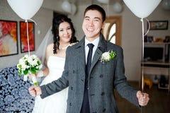 Glücklicher Bräutigam mit Ballonen in seinen Händen, zuhause am Hochzeitstag, die Braut im Hintergrund Lizenzfreie Stockfotos