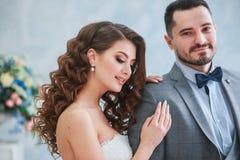 Glücklicher Bräutigam und Braut, die auf einem Studio mit schönem Blumendekor aufwirft Verbinden Sie das Umarmen Lizenzfreie Stockfotos