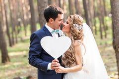 Glücklicher Bräutigam und Braut in einem Park mit Zeichen als Herzen Stockfoto