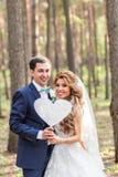 Glücklicher Bräutigam und Braut in einem Park mit Zeichen als Herzen Lizenzfreies Stockfoto