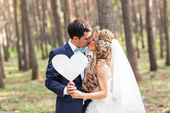 Glücklicher Bräutigam und Braut in einem Park mit Zeichen als Herzen Stockbilder