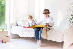 Glücklicher Bruder und kleines Schwesterchen, die ihre Geschenke öffnet Lizenzfreies Stockfoto
